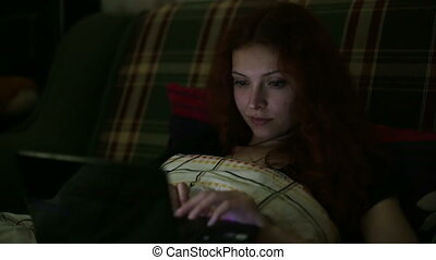 Young woman using a laptop lying on bed at home at night