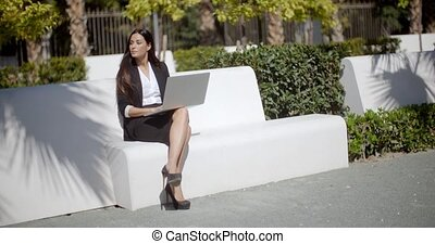 Young woman using a laptop on a white park bench