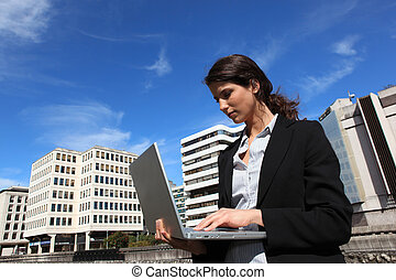 Young woman using a laptop outdoors in the city