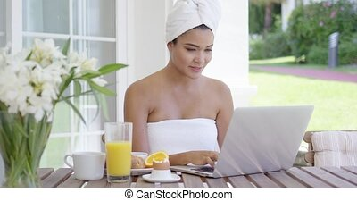Young woman using a laptop while having breakfast