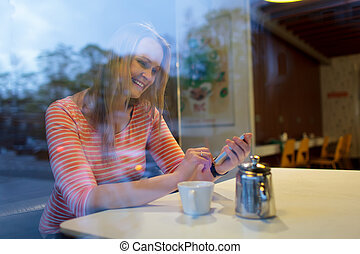 Young woman using a mobile phone in a cafeteria