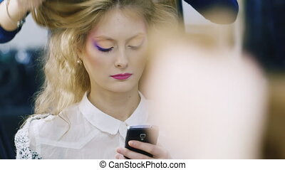 Young woman using a mobile phone in Hairdressers