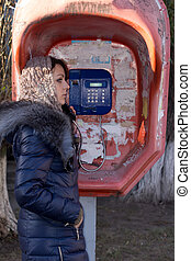 Young woman using a public phone booth