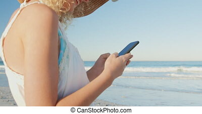 Young woman using a smartphone at the beach 4k