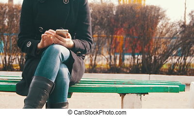 Young Woman using a Smartphone on a Bench in the City Park