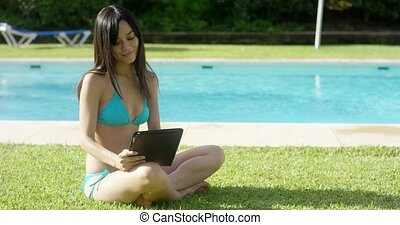 Young woman using a tablet at a resort pool