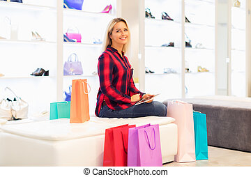 Young woman using a tablet computer in the fashion store -...