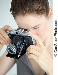 Young woman using a vintage zeiss camera - A woman using a ...