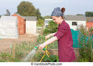 Young woman using  a water hose