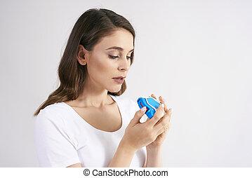 Young woman using an asthma inhaler