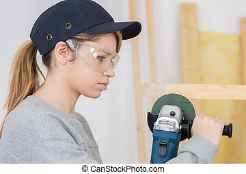 Young woman using angle grinder