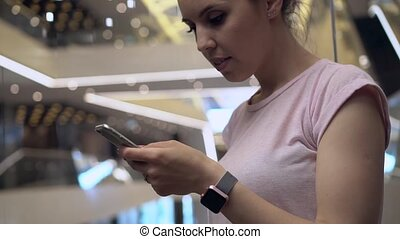 Young woman using app in the smartphone in a moving elevator with bright lights