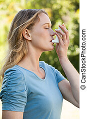 Young woman using asthma inhaler at park - Side view of a...