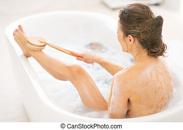 Young woman using body brush in bathtub. rear view