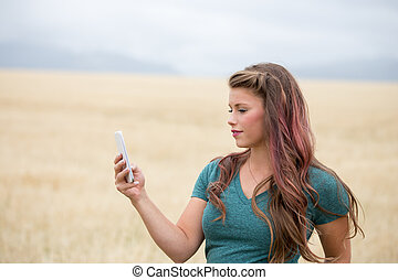 Young woman using cell phone outdoors.