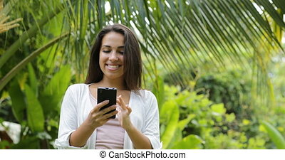Young Woman Using Cell Smart Phone Smiling Looking In Camera...