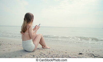 Young woman using cellphone on the beach, dolly shot - Young...