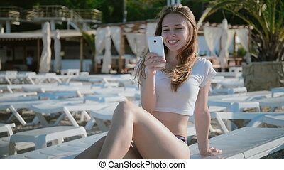 Young woman using cellphone while lying on sunbed on beach -...