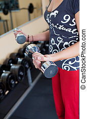 Young woman using dumbbells in a gym
