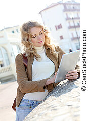 Young woman using electronic tablet in town