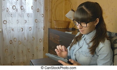 Young woman using electronic tablet sitting in sofa