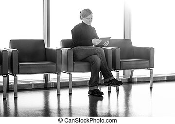 Young woman using her digital tablet pc at an airport lounge, modern waiting room, with backlight.