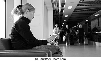 Young woman using her digital tablet pc at an airport lounge.