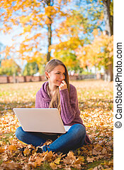 Young woman using her laptop outdoors in autumn