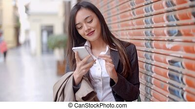 Young woman using her mobile in town