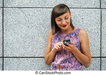 Young woman using her phone in the city smiling.