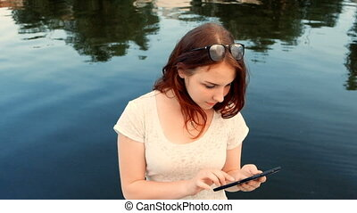 Young woman using her tablet computer while relaxing outdoors in a park on a lovely spring day near river