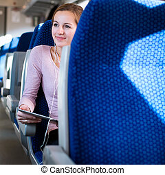 Young woman using her tablet computer while traveling by...