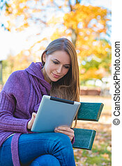 Young woman using her tablet in an autumn park