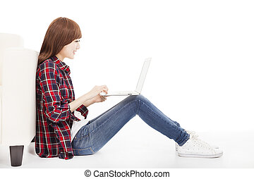 young woman using laptop and sitting on the floor