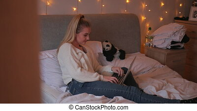 Young Woman Using Laptop at Home - Young woman is sitting on...