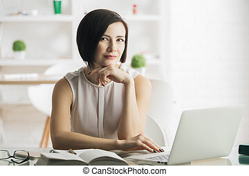 Beautiful thougtful young woman using laptop in modern office