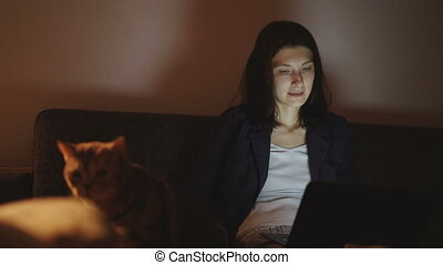 Young woman using laptop computer and stroking the cat sitting on sofa at home in night time