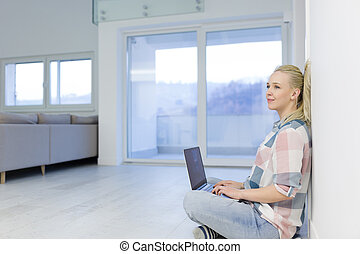 young woman using laptop computer on the floor - beautiful...