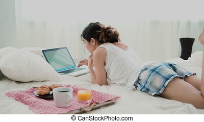 Young woman using laptop during breakfast lying on white bed at home. Brunette girl typing on pc computer.
