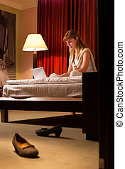 Young woman using laptop in hotel