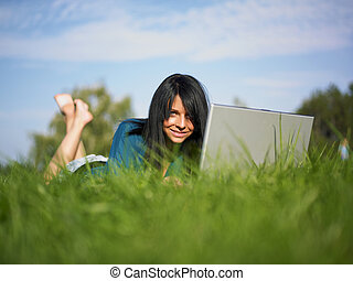 Young woman using laptop in park