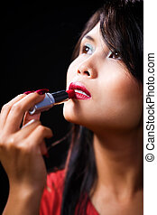 Young woman using lipstick