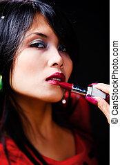 Young woman using lisptick