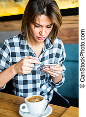 Young woman using mobile phone in cafe