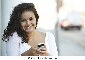 Young Woman using Mobile Phone In Urban Setting
