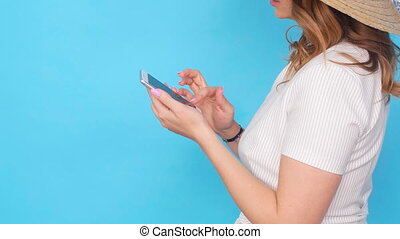 Young woman using mobile phone on blue color background