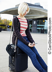 Young Woman Using Mobile Phone While Sitting On Luggage
