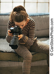 Young woman using modern dslr photo camera