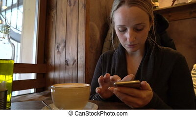 young woman using phone in a cafe