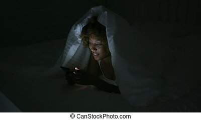Young woman using phone in dark room